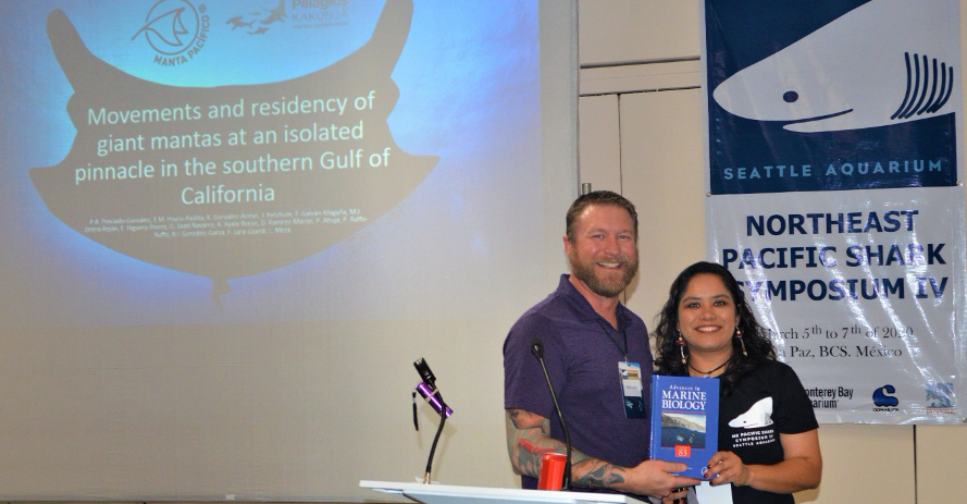 Dayv Lowry presents a copy of the book to a student shark researcher.