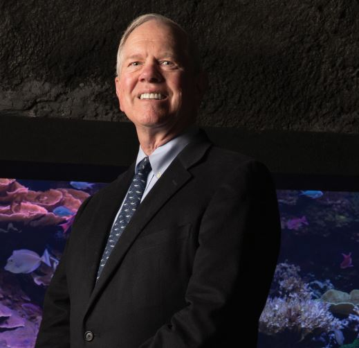 Bob Davidson poses in front of an Aquarium exhibit