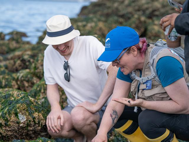 A beach naturalist shows a beach-goer her low-tide finds