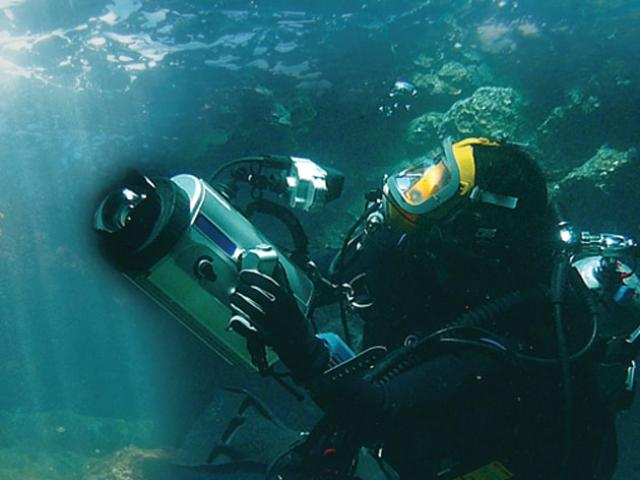 Diver holding an underwater camera.