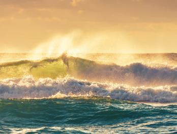 Ocean waves crashing during sunrise.