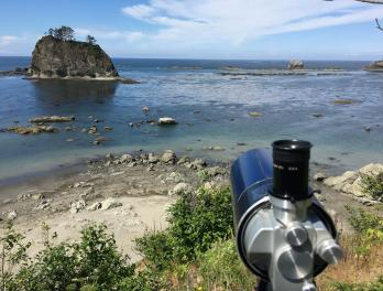 Spotting scope on a hill overlooking the ocean